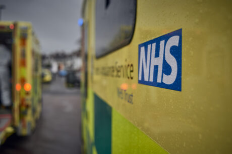 The side of an ambulance showing the NHS logo