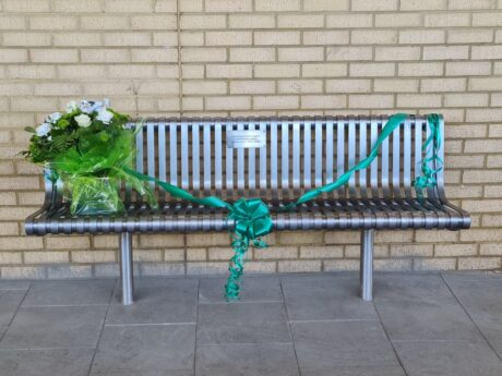 The memorial bench with a bouquet of flowers