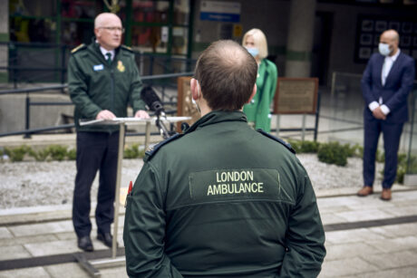 The rear of an ambulance crew's jacket which reads ambulance as he watches a speech being made