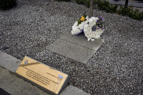 A flower wreath at the foot of the memorial tree and an engraved plaque