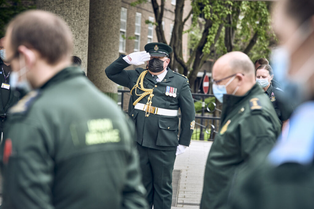 A member of the ceremonial unit salutes as staff observe a minute's silence