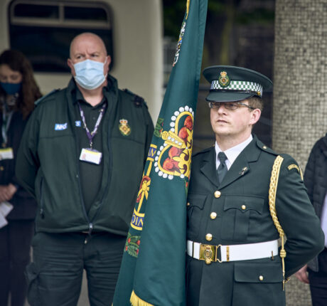 A member of the ceremonial unit holding the Service commemorative flag