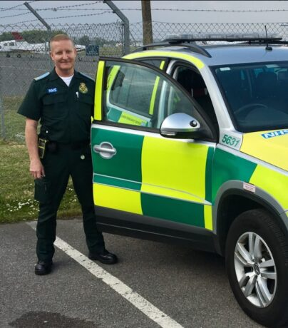Tony in LAS uniform next to an ambulance car