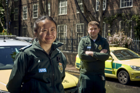 Joyce and Ben in LAS uniform smiling in front of a response car