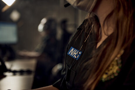 a call taker photographed with the NHS logo on their t-shirt