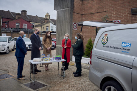 HRH The Duke and Duchess of Cambridge alongside LAS staff including Tea Truck operator Shani are shown a Tea Truck which is parked with rear door open and a table of refreshments