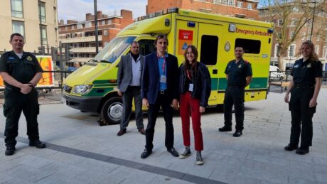 Nicolas and Alaia (front) with medics (from left) John, Vijay, Junaid and Kirsty stood in front of an ambulance