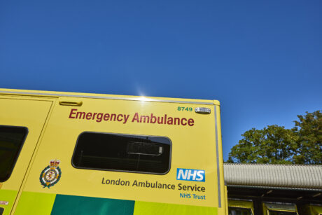 The side of an ambulance parked in an ambulance station with sunny blue sky in the background