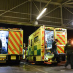 A row of ambulances in an ambulance station from the rear with crews getting kit ready