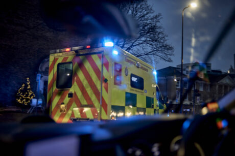 An ambulance with blue flashing lights shown driving from another vehicle following behind's cab