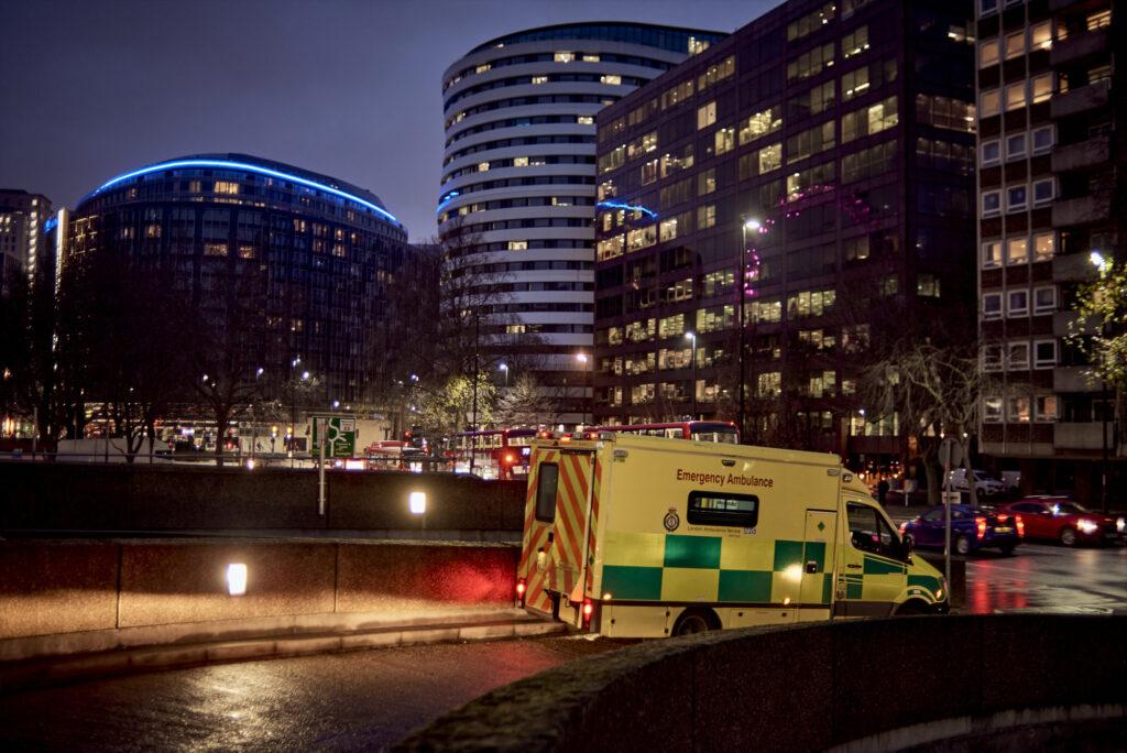 An ambulance leaving a hospital ramp at night