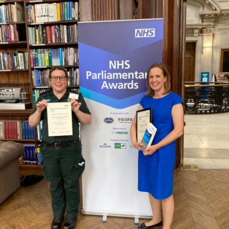 Carly from the LAS mental health team and Georgina from the End of Life care team holding their certificates in front of a banner that reads NHS Parliamentary Awards