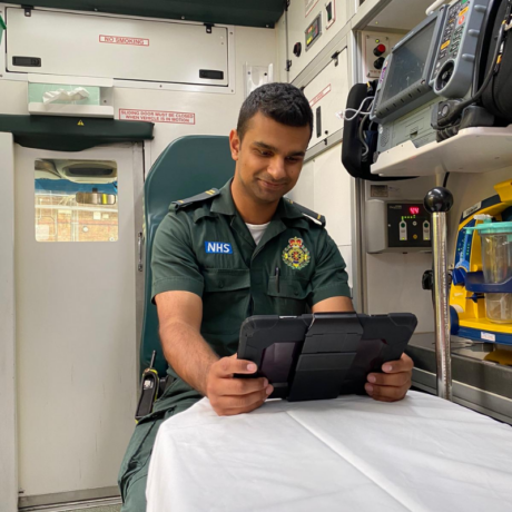 A medic sat on a seat in the back of an ambulance uses an iPad
