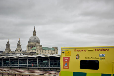 St Paul's Cathedral and City skyline in background and corner of an LAS ambulance in foreground