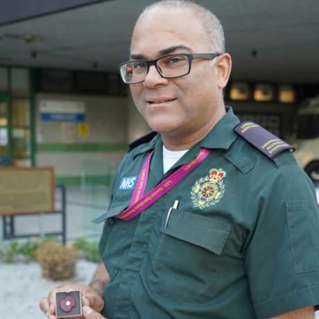 André in his Service uniform holding one of the poppy badges