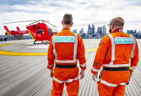 A doctor and flight paramedic in their flight suits on the helipad with the Air ambulance in the background