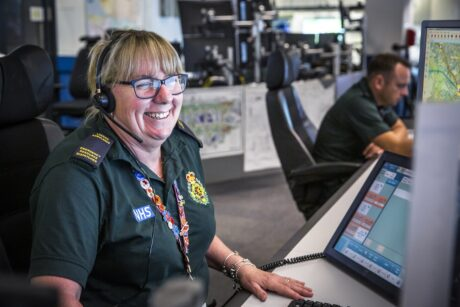 Mandy smiling at her desk with a headset and looking towards a screen in the control room
