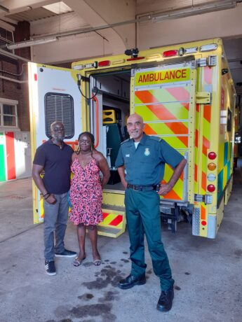 Paramedic Raj Mann with Omar's parents, Diane and Jeff in front of an ambulance