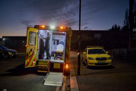 An ambulance and ambulance car parked next to each other in a dark street. The ambulance rear doors and lift are open and down and a paramedic is shown in the back