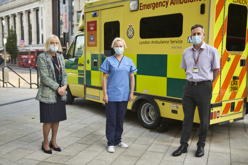 Heather Lawrence, Ruth May and Daniel Elkeles in front of an ambulance