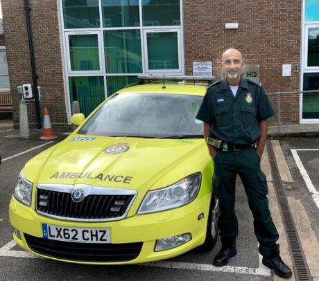 Paramedic Raj Mann stood in uniform next to an ambulance car