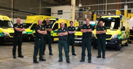 Stuart Law with colleagues from TRU and HART in a group in front of a range of ambulance vehicles