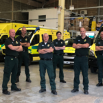 Stuart and his colleagues stood in a group in an ambulance base for a group photograph