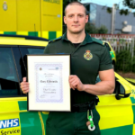 Gary Edwards in uniform stood in front of an ambulance car holding a certificate
