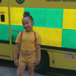 Ariana smiling photographed stood in front of an ambulance