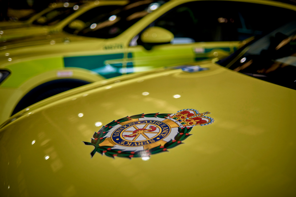 Decorative image showing the LAS crest on the bonnet of an ambulance car