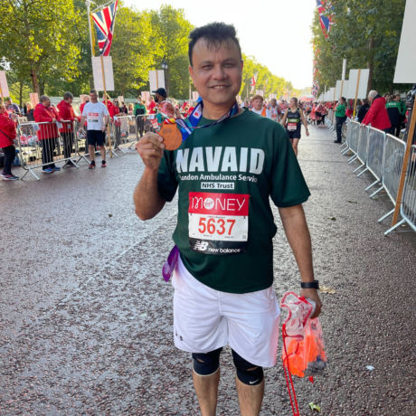 A runner at the end of the London Marathon holding their medal with their running vest visible, which reads their name and that they're running for the London Ambulance Service