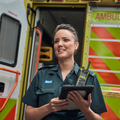 A medic holding an iPad with an open ambulance rear door behind her
