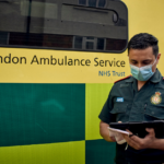 A medic stood in front of an ambulance using an iPad